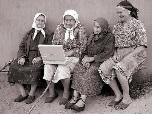 Four elderly women look at a laptop computer